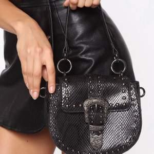En snygg handväska från Fashion Nova, väskan är i fejk läder med orm print i färgen svart. Väskan har en kedja som axelband samt har den ett mindre handtag upp till på väskan. Väskan har nitar och ett stort spänne fram till vilket gör det lilla extra på väskan. Väskan är helt ny och ligger kvar i sin original förpackning.  Köpare står för eventuell frakt!