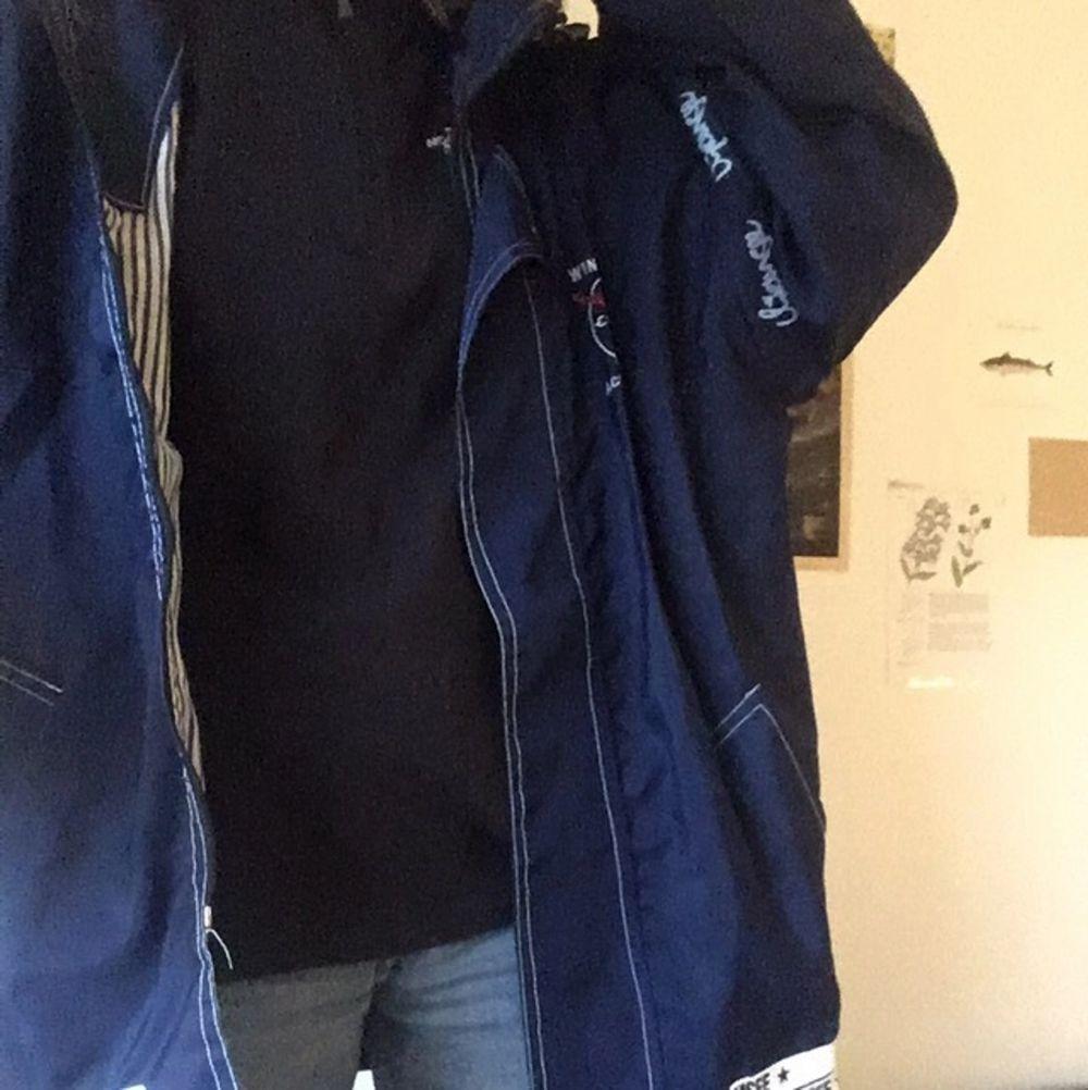 Supercoola mörkblå vindjacka med broderat märke på rygg och randigt innertyg. Skyddar mot både regn och vind. Har avtagbara ärmar och luva. Passar stl XS-XL beroende på önskad passform (själv är jag xs). Jackor.