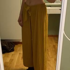 Mjuka och luftiga utsvängda byxor i gult. Är lite korta i storleken. Super mysiga att ha!