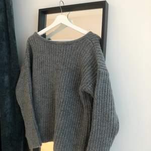 Stor grovstickad tröja från NAKD. Mörkgrå färg och med en V ringning i ryggen.
