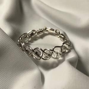 Handgjord ring, flätad med pärlor i. Innerdiametern är 16mm. (Den är silverpläterad, så undvik att tvätta händerna med den på)