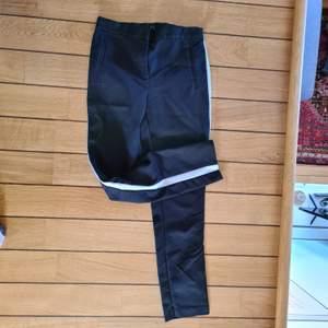 Svarta kostymbyxor med vita revärer längs sidorna. Mjuk och skön linning. Två fejkfickor bak. I mycket gott skick och stark svart färg (första bilden är mer rättvis färgmässigt).