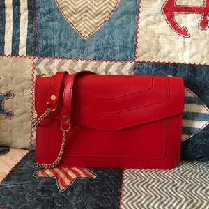 Never worn red leather bag with gold hardware. Bought from Italy. Has a small barely noticeable pen mark on the flap, please see the last photo. This could be easily covered by a pin or scarf.