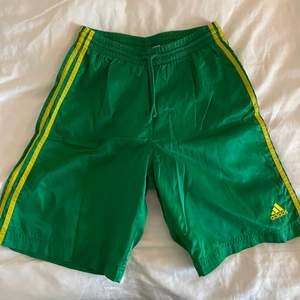 Vintage adidas shorts i den ikoniska gula och gröna färgkombon. Lite slitna i tyget (skriv för bild), annars fint skick. Bortklippt storlekslapp men sitter som en xs-m. Bild 2/3 är lånade, lite inspiration. Frakt tillkommer