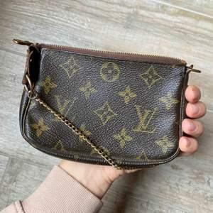 Louis Vuitton mini pochette i fint skick, slitning vid tagen Louis Vuitton. (se bilder för mer) Annars i bra skick.  Sparsamt använd!