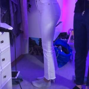 Vita jeans från zara som är kort i modellen med utsvängning nedtill. Storleken är 34.