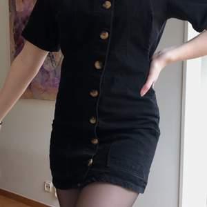 Svart jeanskläning med knappdetaljer