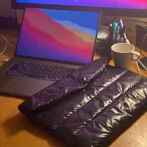 """TONICELLA UF. Datorfodral i nylon, vadderat med dun. Facket är stort så det går utan problem att få ner ett skrivblock eller laddare ink. dator. Passar bärbara datorer upp till 16"""". Höjd 31 cm, bredd 40,5 cm"""