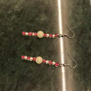 Detta är ett par örhängen som innehåller en självlysande pärla och några andra rosa och vita. På sista bulldeg så måste du dra upp ljusstyrkan på telefonen för att se. Men det är när pärlorna lyser i mörkret!