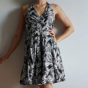 Rockabilly inspirerad halterneck klänning ifrån H&M, stl.36. Fin och somrig, har använt tillsammans med ett rött lackskärp ibland. Knyter i nacken. En svart tyllrand längst ner på den svarta underkjolen. 🙂 Smockad tyg i ryggen.
