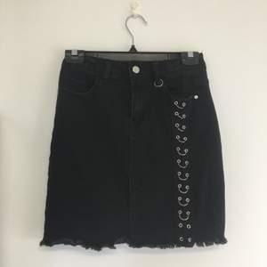 Svart kjol med slitna detaljer och metallringar.