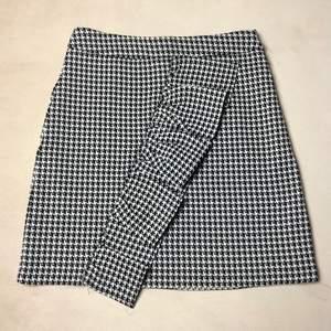 Kort kjol med hög midja. Fint volang framtill, stretchigt material och använd max 2 gånger. Säljer pga viktuppgång.