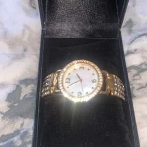 Den är helt ny aldrig använd, har varit en present. Kostade 400kr som ny. Guldig med stenar över hela klockan och vit pärlemor i uret.