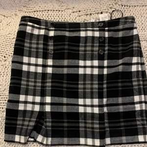 """Rutig kjol med prydnadsknappar  Snygg rutig kjol med prydnadsknappar fram och dragkedja i sidan.  Aldrig använd endast prövad . Köpt på bonprix för 199 kr &!säljs fortfarande där under """" rutig kjol """" om du vill se fler bilder :)"""