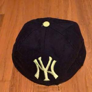 Yankee keps utan en brim helt enkelt, justerbar på baksidan. Mörkblå och ljusgrön. Riktigt snyggt på gädha. Buda i kommentera