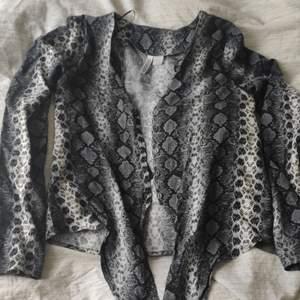 Blus med ormskinnsmönster från H&M divided inköpt för c:a 1 år sedan, knappt använd. Väldigt fin att ha nu till våren, tunt material.
