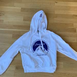 En vit hoodie i storlek S från H&M. Står paramount på trycket.