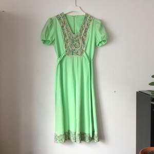 Mintgrön vintageklänning med blommiga bårder. Blixtlås  i metall, så bör vara 60-tal, -68? Hemsydd, troligen efter mönster i nån tidning. Har släppt pyttelite i sömmen runt midjan, (se bild).