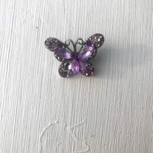 Söt lila fjärilsbrosch från tidigt 2000-tal. Vissa stenar saknas på broschen som man kan se på bilden därav de billiga priset, detta går säkert att fixa om man verkligen vill det. Frakt kostar 11 kr.