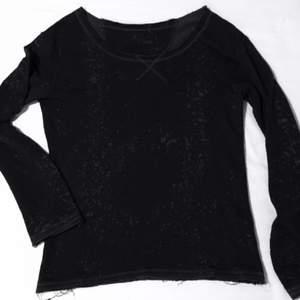 Mörkgrå Mjuk och lite mer hängande tröja med stor hals och detaljer i form utav stänk som är i ljusare grå ton. Alla tyg ändor är
