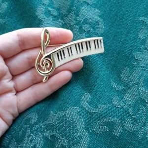 Musik-brosch säljes, 25 kr inklusive frakt eller högstbjudande! Färgen är nött, men går ju att fylla i tangenterna om en har färg som fäster. 😊