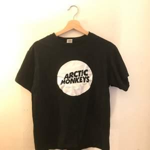 Svart t shirt med tryck av bandet arctic monkeys, bra band, den sägs vara i storlek L men passar mer likt en small/medium