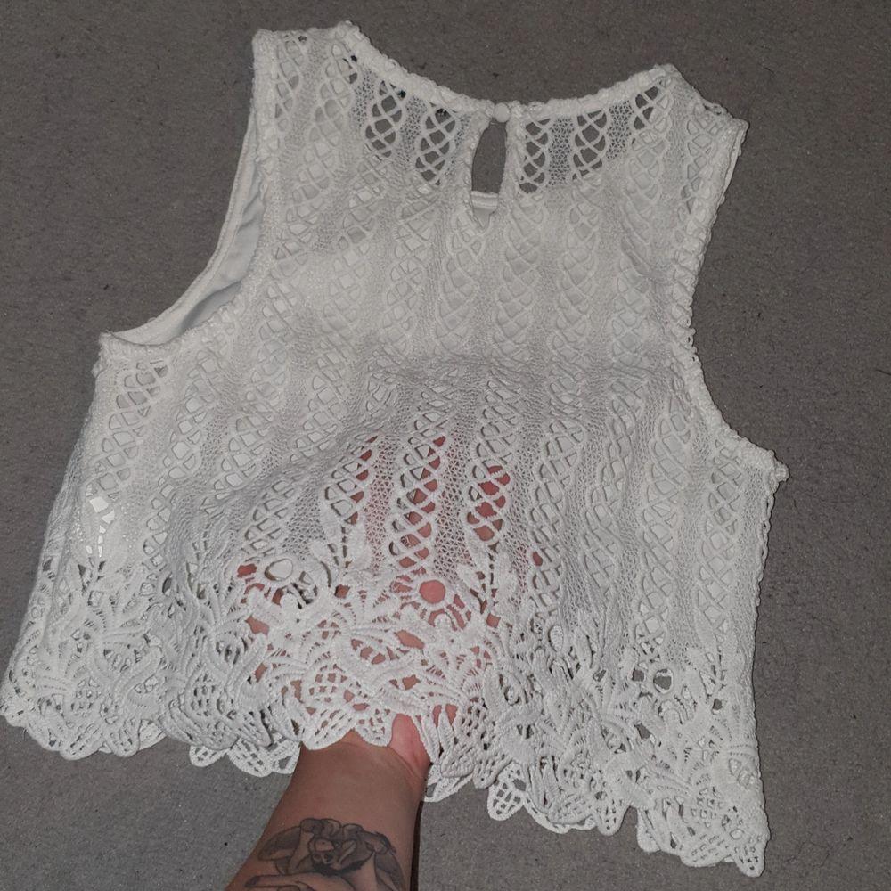 Ett gulligt vitt typ virkat linne.  Genomskinligt på ryggen,kortare som typ en crop top går ungefär till naveln. Köparen betalar frakt 44kr :). Toppar.