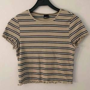 Randig beige T-shirt från Gina Tricot i storlek L. 100 kr inklusive frakt