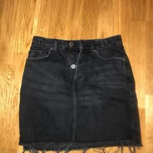 Snygg svart kjol med silvriga knappar. Storlek 34. Köpt ifrån H&M. En väldigt cool sliten svart färg med slitningar nedantill.