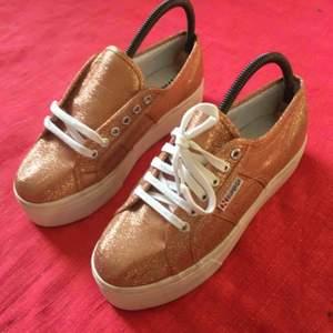 Helt oanvända sneakers med platå från märket Superga. De är bronsfärgat glittriga och riktigt snygga till ett par brunbrända ben i sommar ☀️ 300 plus frakt!