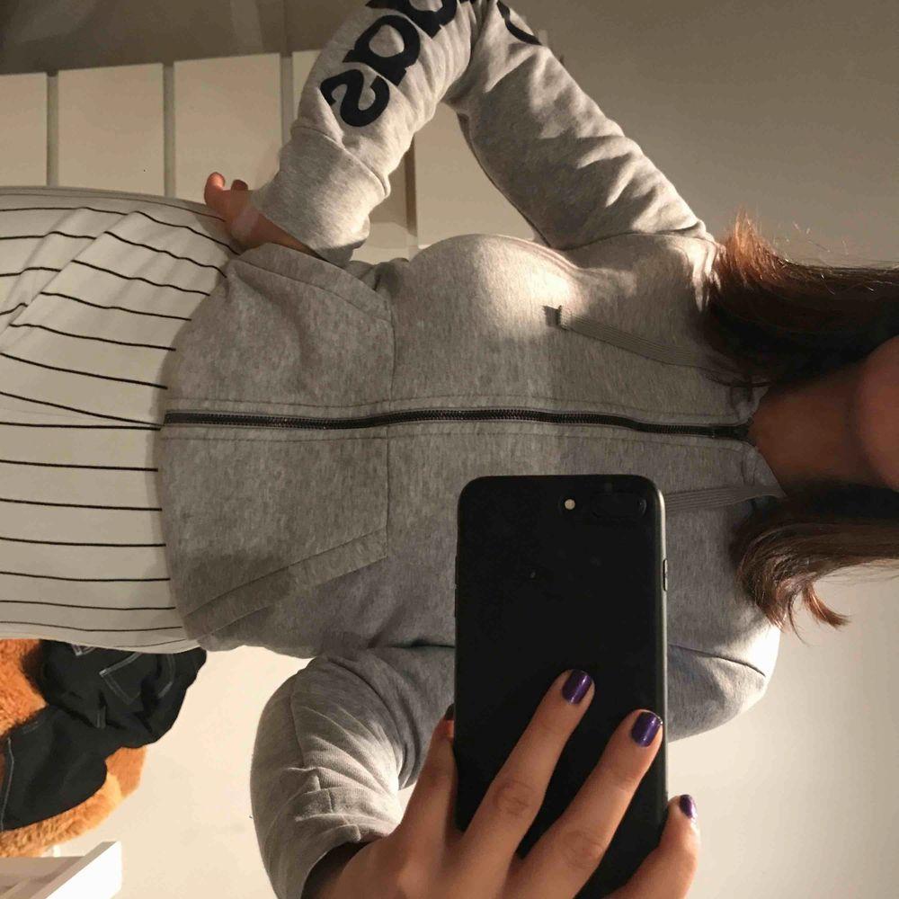 En grå adidas kofta som passar både XS och S . Huvtröjor & Träningströjor.