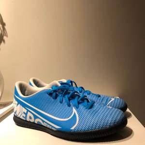 Ett par Nike innomhus fotbollsskor i storlek 41, men är väldigt små i storleken så dem skulle sitta bra på någon med storlek 40 jag eller storlek 40.5. Dem är blåa och är i fint skick (använda enstaka gånger.) Det finns en liten fläck inuti ena skon men är ingenting man ser vid användning. Vid ditt köp kommer dem att vara tvättade utanpå och även tvättade skosnören. Allt som tillhör skon är orginal. Skorna kommer skickas via posten och ni står för frakt. Säljer dessa för att dem är för små och med nedsatt pris.                      Skriv till mig om du har någon fråga.                Mvh, Maja Forsgren