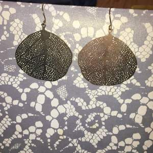 Guldfärgade guldörhängen med form av ett blad. Kan lätt användas till fest men lika lätt till vardag. Säljes för att det inte är min stil att bära.