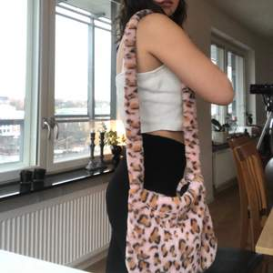 Rosa mjuk väska med mönster på. Svart innefoder.