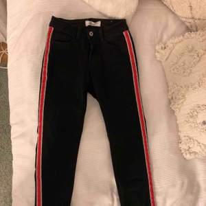 Svarta jeans med röd rand på sidan av benen, köpta från Chelsea i storlek 36. Nästan helt oanvända!  Köparen står för frakt!