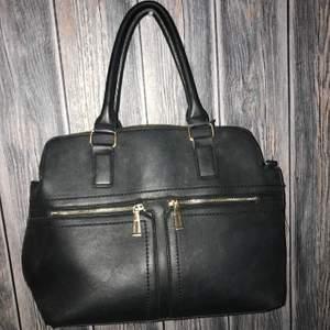 Svart handväska med gulddetaljer. 100kr. Köparen står för fraktavgiften.