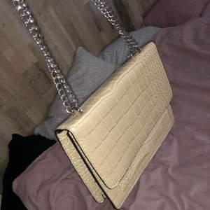 Beige väska från Nelly med silverkedja och ormskin detaljer, har aldrig använt den, den ligger bara i garderoben