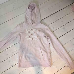 Ljusrosa hoodie från HM med städer tryckta i vit och roseguld. Storlek XS men passar även S, jättebra skick. Snöret i luvan fattas tyvärr. Köpt för 300 kr ungefär