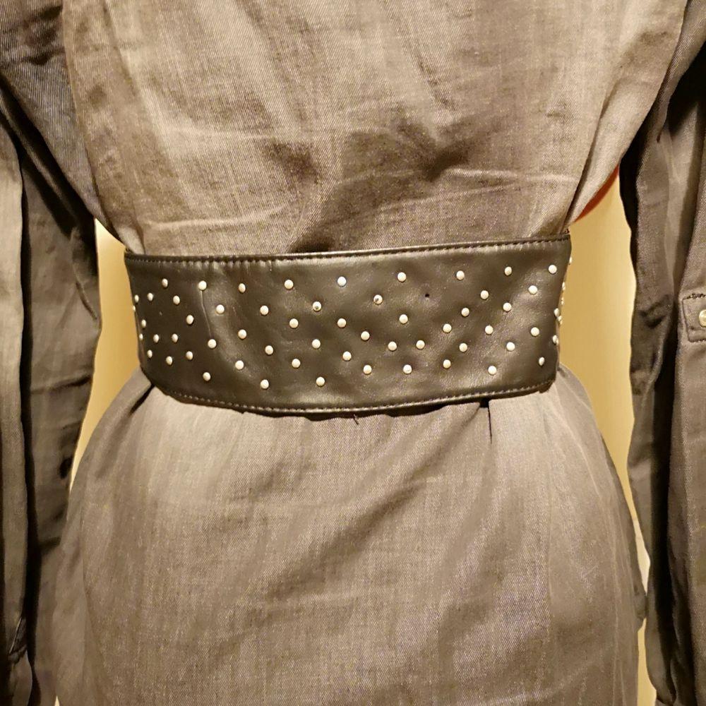 Midjeskärp i grå skinnimitation med elastiska band och 3 knappar för knäppning framtill. Hela skärpet är 71 cm långt fram till knäppet när det är utsträckt avslappnat. . Accessoarer.