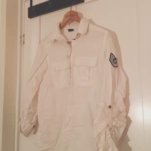 Vit, ganska lång skjorta i ett ganska tjockt material. Har ett emblem på ena ärmen. Från Gina tricot