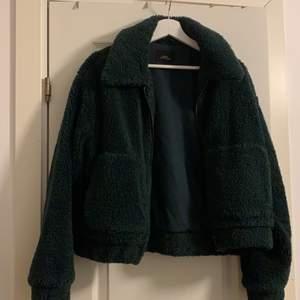 En Teddy jacka i grönfärg, jackan är i ett bra skick. Jackan är lite större i storleken så funkar som en M också.