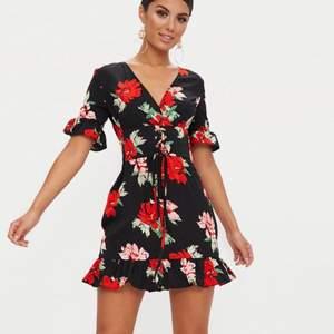 En blommig klänning från PrettyLittleThing med korsettliknande bälte runt midjan. Aldrig använd.