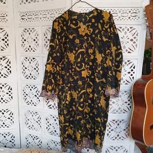 vacker klänning i svart med gul/guldigt blommönster! står ej material men det e luftigt å tunt men inte genomskinligt! spetsdetaljer i silvrig/rosaskiftande tråd!