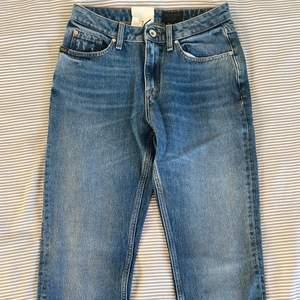 Ett par blå nya Tiger of Sweden jeans med prislapp kvar. Dem är raka och är regular i midjan.
