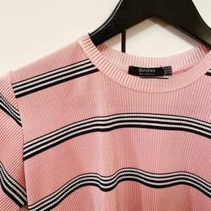 Säljer en T-shirt i glansigt, lite räfflat tyg, från Bershka. Oanvänd. Köparen står för frakt
