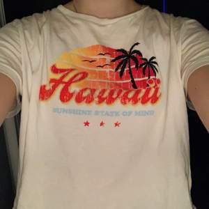 """Mjölkvit T-shirt med färgglatt Hawaii-tryck på framsidan från H&M i strl L, passar dock som lite oversized S (jag har strl S i vanliga fall). Inget tryck på ryggen. Den är lite croppad, alltså inte lång som en vanlig t-shirt, men inte """"magtröja-shape"""", framförallt inte om man använder den som oversized S. Bara använd 1 eller 2 gånger och inget slitage, så skulle säga att den är i nyskick. Kan köpas direkt för 100kr exkl. frakt (ca 60kr)."""