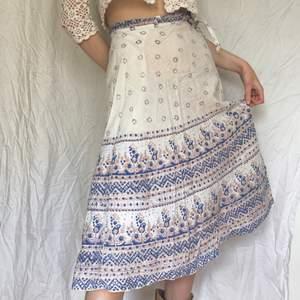 Superfin och unik vintage omlottkjol i 70-tals / boho stil, Vit med vackra mönster i blått/beige. Skönt lätt tyg i typ bomull eller linne som är perfekt till sommaren. Jag som har på mig kjolen är 179cm lång S, men den passar typ alla storlekar då den är omlott.
