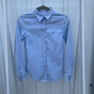 En ljusblå figursydd skjorta från GANT med ett broderat märke på höger bröst. Den är i väldigt fint skick men i akut behov av att strykas;) Jag skulle tippa på S men vet inte helt säkert pågrund av avklippt lapp.