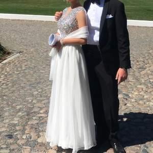 Säljer min vita balklänning med sjal. Den är otroligt fin och bara använd vid ett tillfälle. Är köpt på Pink and Purple. Är skräddarsydd nedtill, jag är 162cm och klänningen är storlek s. Är en inbyggd bh i klänningen.