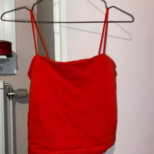Säljer ett kort rött linne från Gina Tricot i Storlek S. Endast använd 1 gång